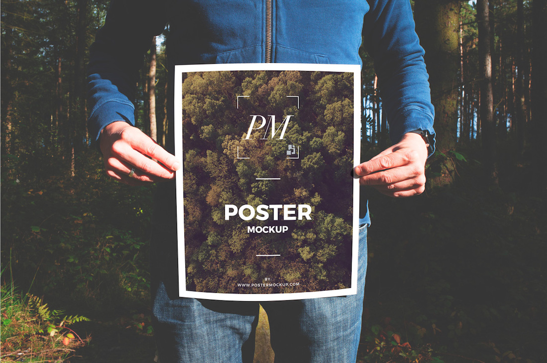 man in forest holding poster mockup